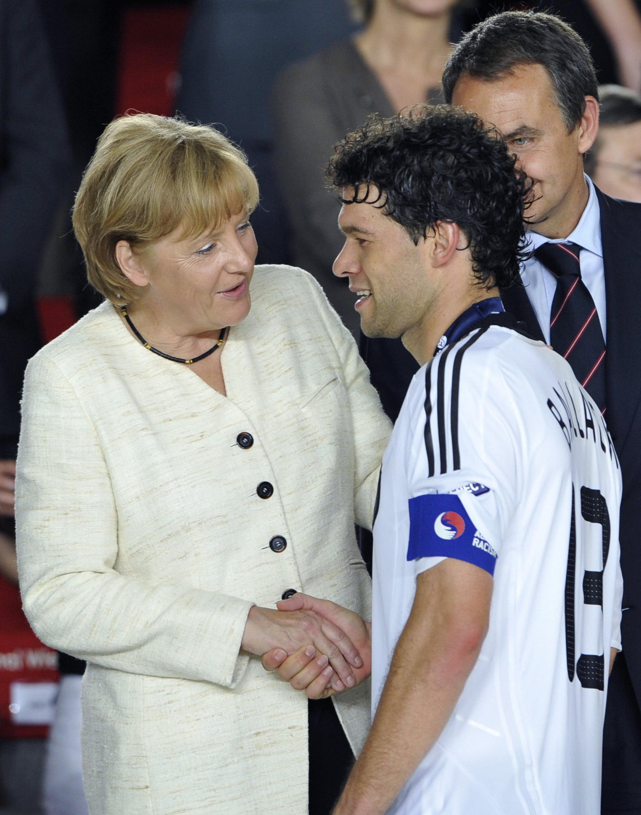 Better luck next time. German Chancellor Angela Merkel shakes hands with German midfielder and captain Michael Ballack.