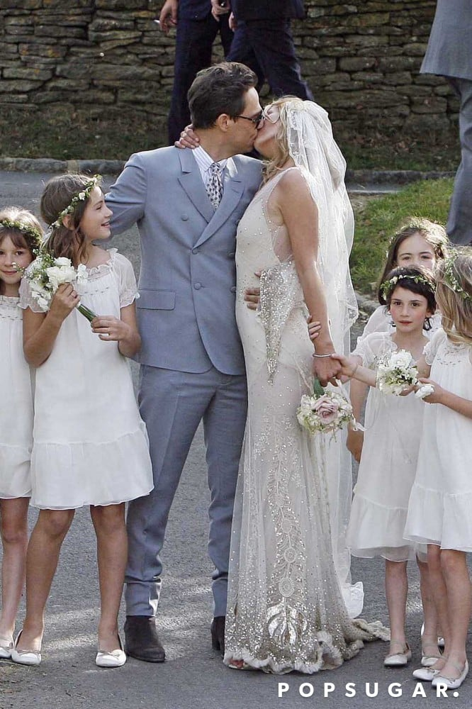 Jamie Hince and supermodel Kate Moss, wearing John Galliano, posed for a kiss following their July 2011 wedding ceremony in England.