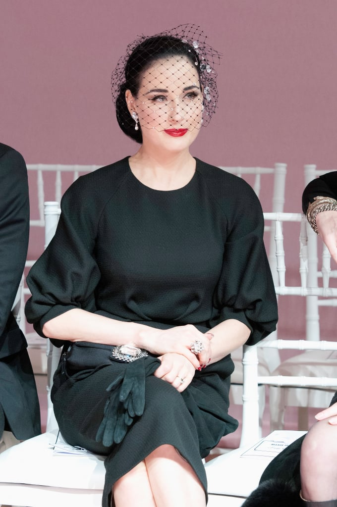 Dita Von Teese's front-row look at Alexis Mabille was all about the accessories: a netted face veil, diamond drop earrings, a sparkly cocktail ring, black gloves, and an embellished black bag.