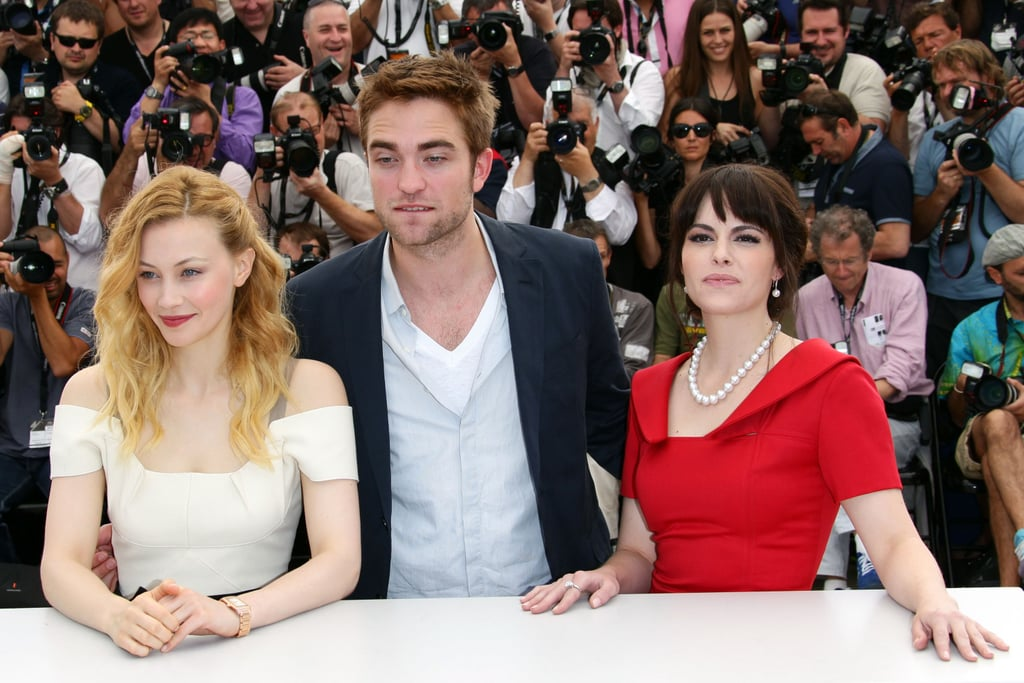 Robert Pattinson posed between costars Sarah Gadon and Emily Hampshire at the Cosmopolis photocall in Cannes.