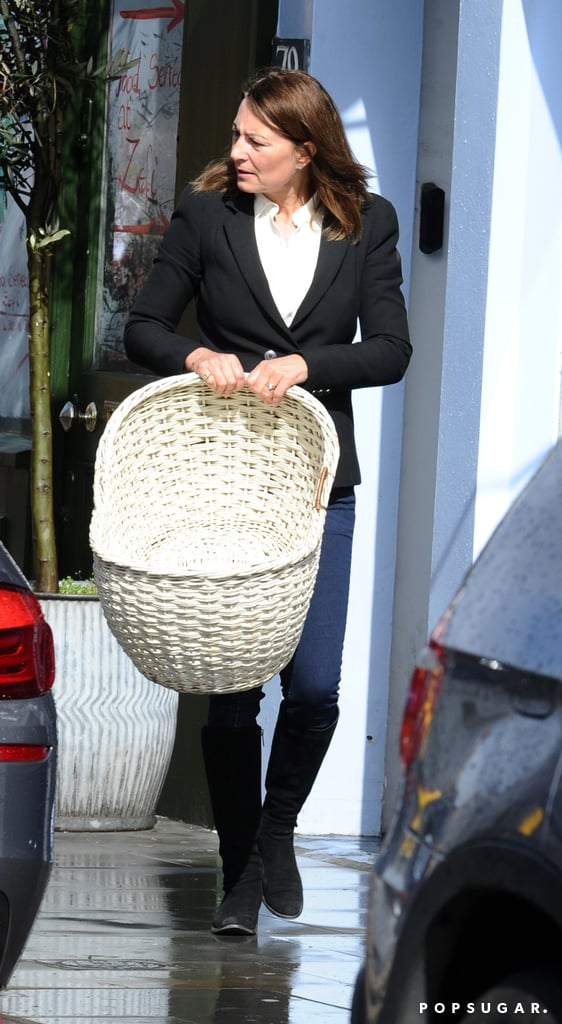 Carole Middleton carried a white bassinet.