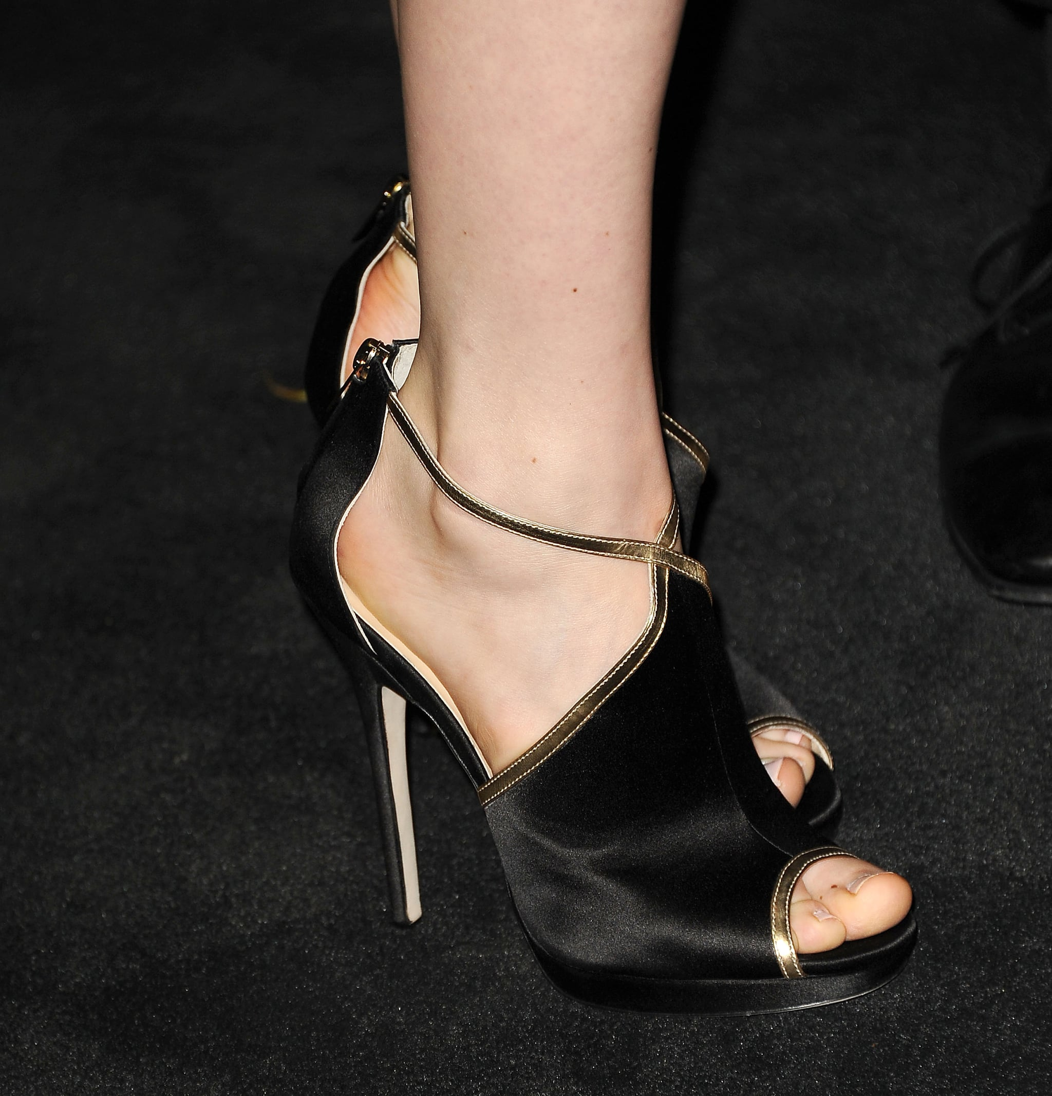 Bella Heathcote added edge to her floral Chanel dress with black-and-gold Jimmy Choo sandals at Chanel's bash.