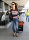 Alessandra Ambrosio got ready to take off from LAX in a colorful striped Whetherly top, ripped boyfriend denim, and black ballet flats. She completed her travel style with a black leather jacket, gradient sunglasses, a bright orange Gerard Darel tote bag, and an armful of bracelets.