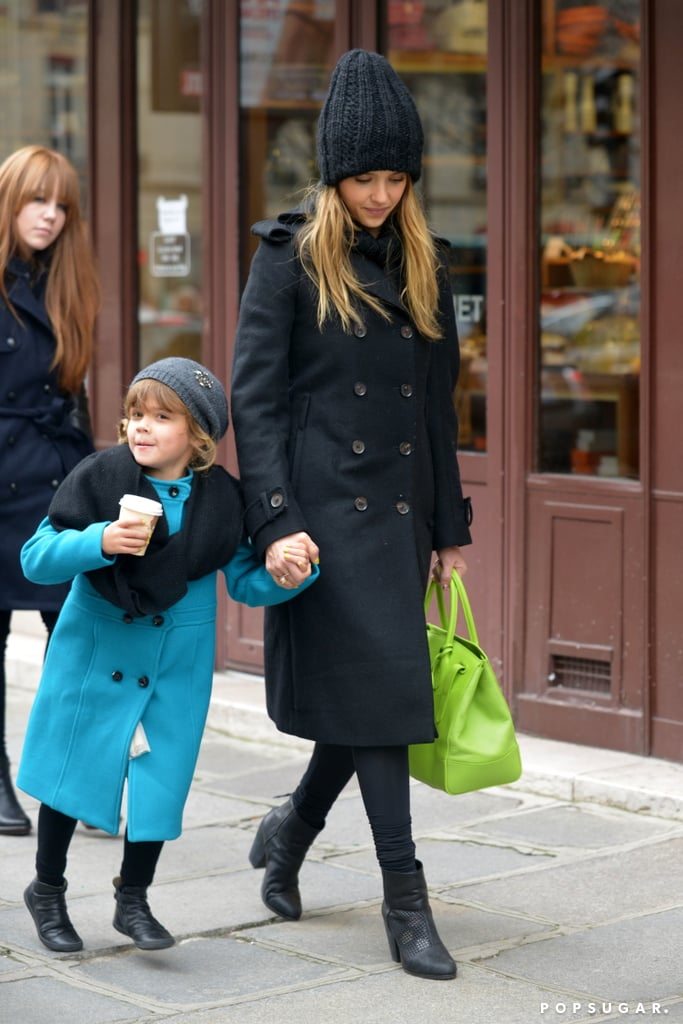 "For a day of shopping with little Honor, Jessica stepped out in an all-black ensemble that screamed ""Parisian elegance"". We're loving this outfit, from the Salvatore Ferragamo wool knee-length coat to her thick cable-knit beanie — snap up this similar Bop Basics Thick-Knit Beret ($58) to copy her cozy look. She injected a cool pop of color into her look with a lime green Ralph Lauren Soft Ricky Bag ($3,500), which added a beachy California-girl vibe."