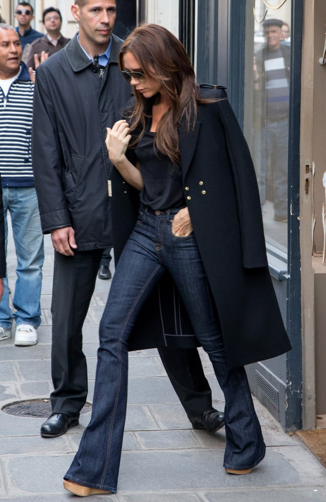During the same Parisian getaway in May, Victoria swapped her light-wash wide-leg denim for a darker pair, then pulled in a black tee, a black military-style coat, and wooden platform sandals. Shop these similar 7 For All Mankind Kaylie Midnight jeans ($169) to nail Victoria's streamlined look.