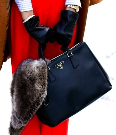 A chic black Prada tote provides maximum contrast against red trousers.