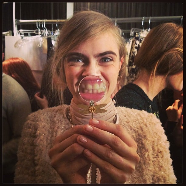 Cara Delevingne goofed around with a magnifying glass necklace at Tory Burch. Source: Twitter user Caradelevingne