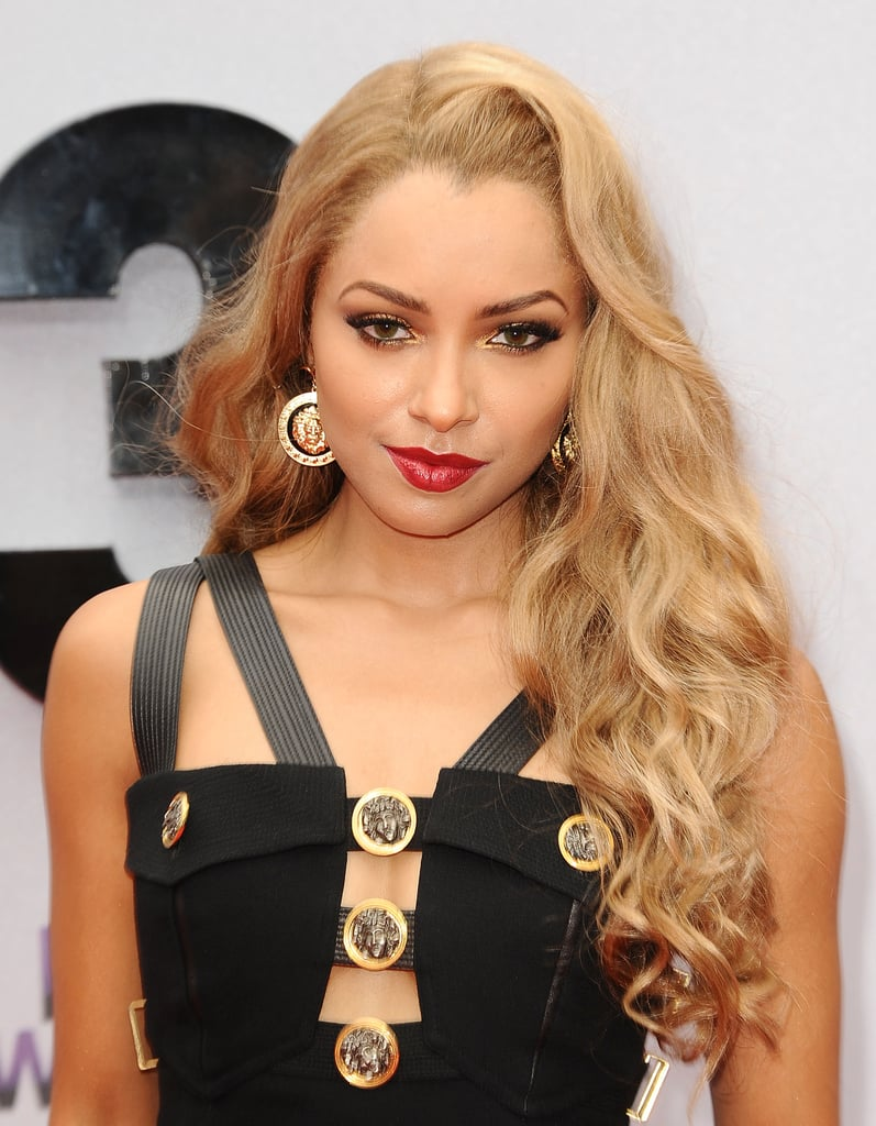 Kat Graham's long blond hair was styled in textured waves, while her makeup was a duet of gilded eye shadow and red lipstick.