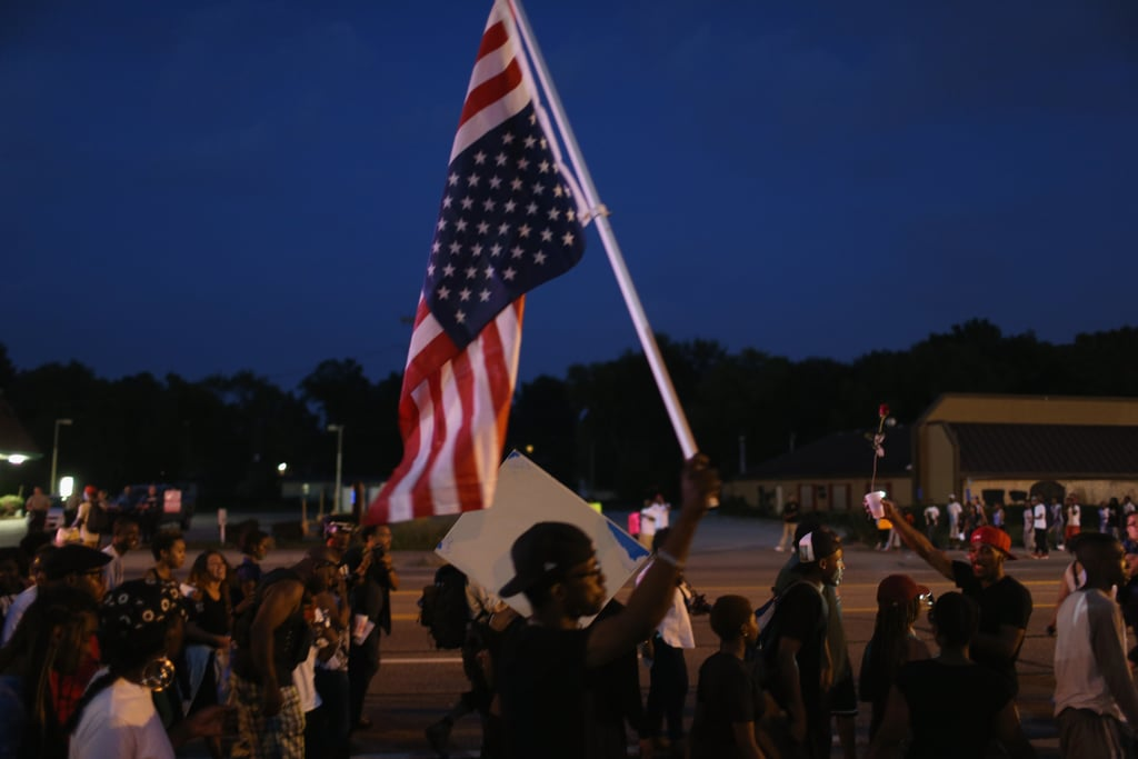 A man held an upside-down American flag during a protest.
