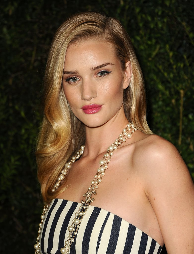 Channeling some of that old-school Chanel glamour, Rosie Huntington-Whiteley wore long strands of Chanel costume pearls with her striped jumpsuit.
