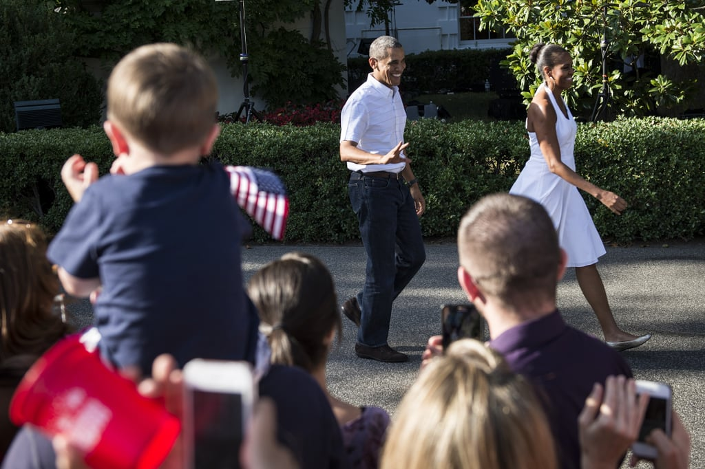 Onlookers waved their American flags as the president and first lady greeted people at the White House in 2014.