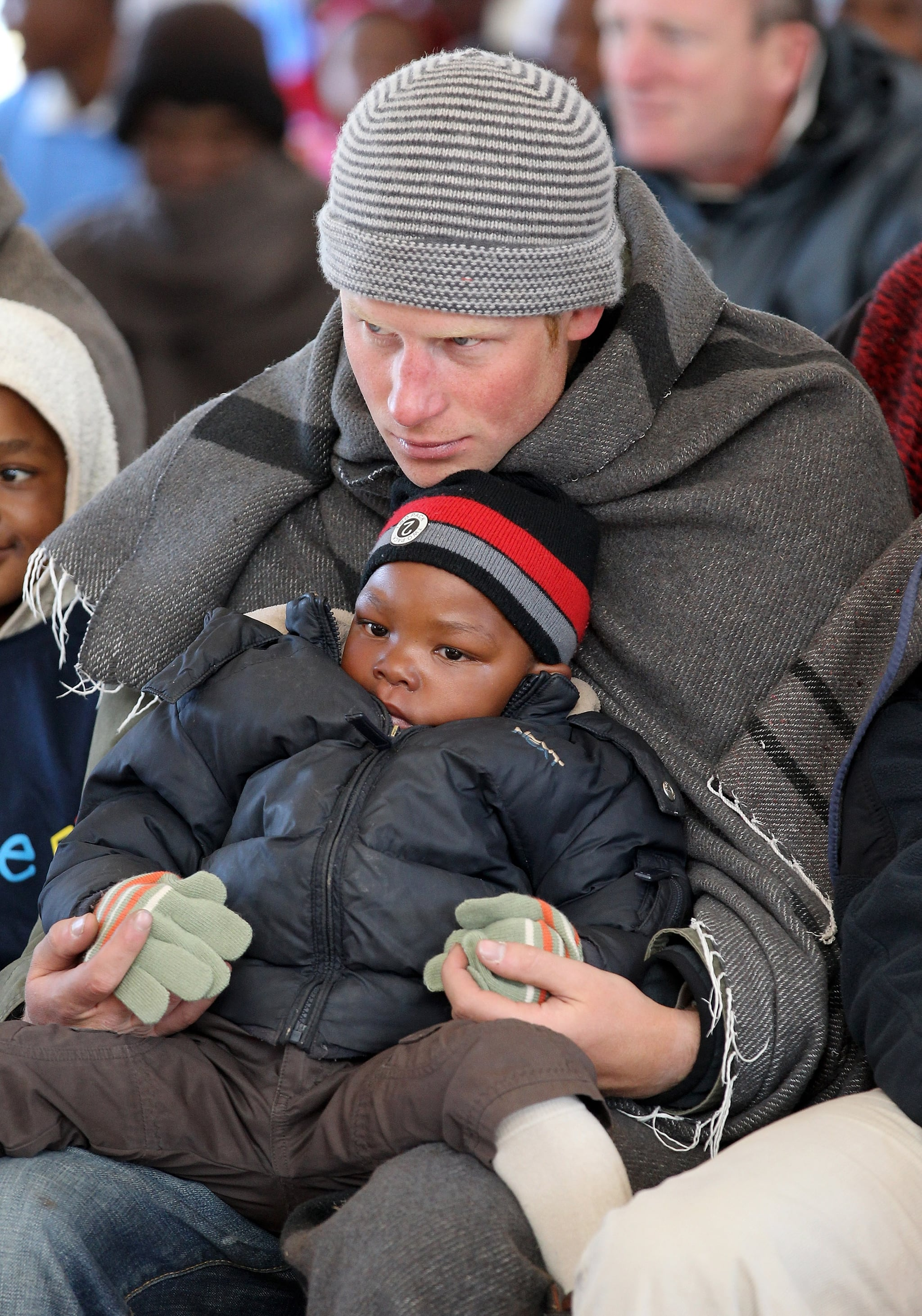 Harry joined hands with a little boy during a visit to a children's center in  Semonkong, Lesotho, in June 2010.