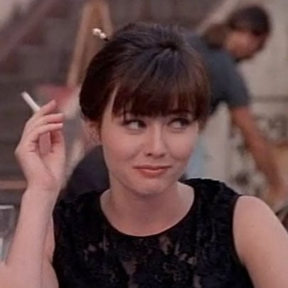 Brenda smokes her first cigarette in France, where she also uses sticks to keep her bun in place.