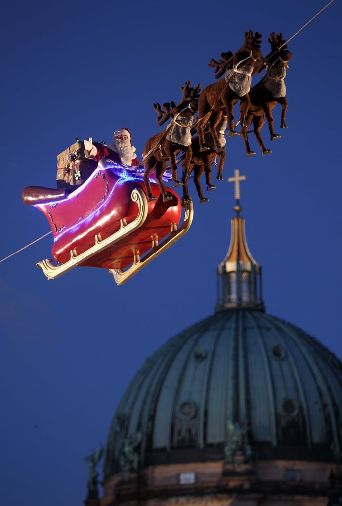 An actor dressed as Santa Claus waved from a suspended sleigh over a Christmas market in Berlin.