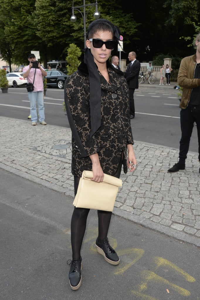 This Berlin beauty covered up in a lace coat, lace-up flatforms, a netted fascinator, and a buttery leather clutch.