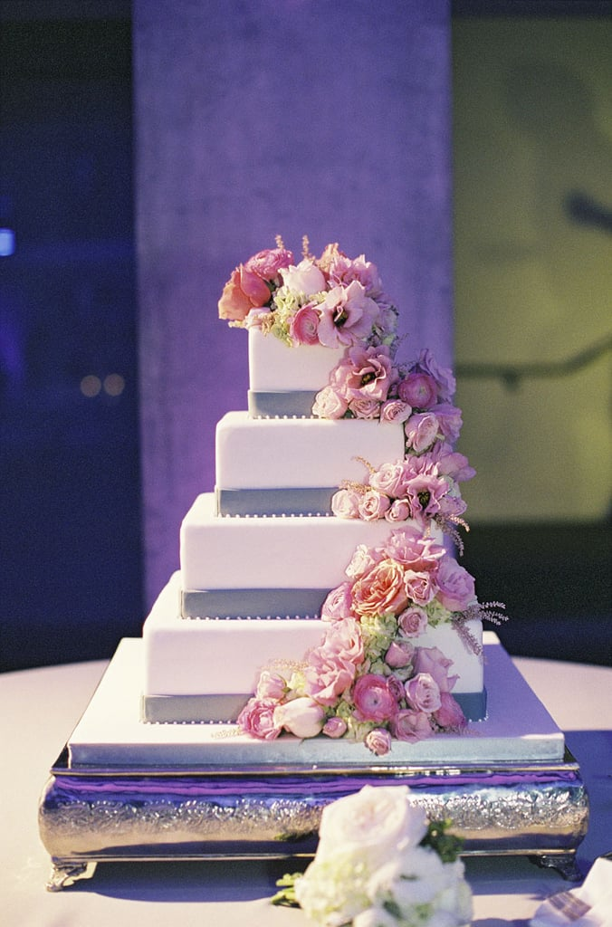 The cascading flowers, purple accents, and four tiers of pretty make this one showstopping cake.