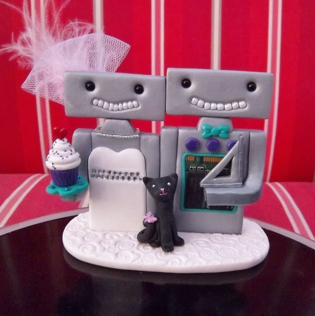 Geeky couples can add a few of their favorite passions (like cats, math, and cupcakes) with Buttoneyedteddybear's Custom Robots Cake Topper ($75).