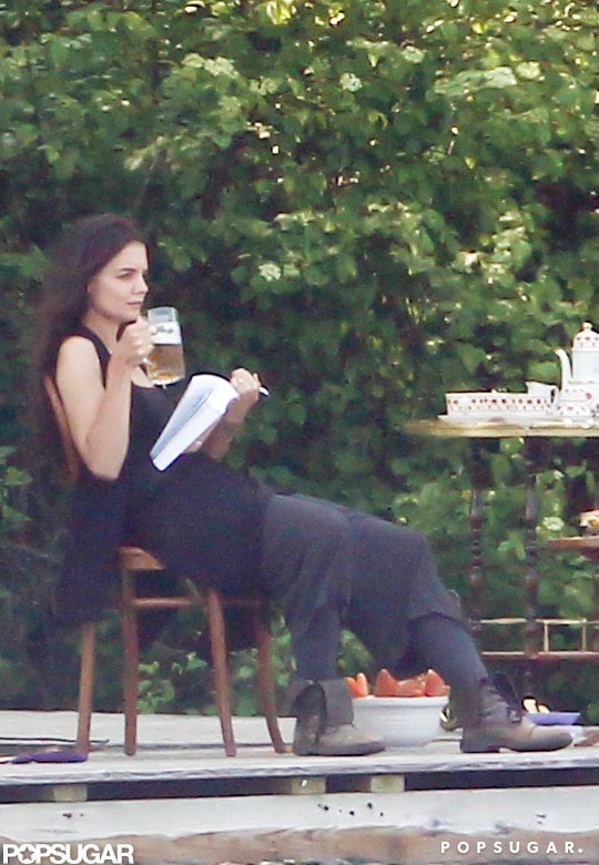 Katie Holmes drank a beer on set while holding a book for a scene.