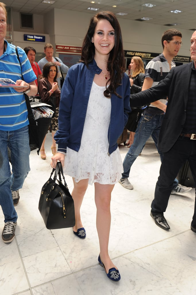 Lana Del Rey made this frilly Summer dress airport-appropriate with a varsity-style jacket, leather weekender, and sensible (but cute!) flats. The bonus: this look goes straight from the airport out to drinks, dinner, or sightseeing without a longer pit stop at the hotel.