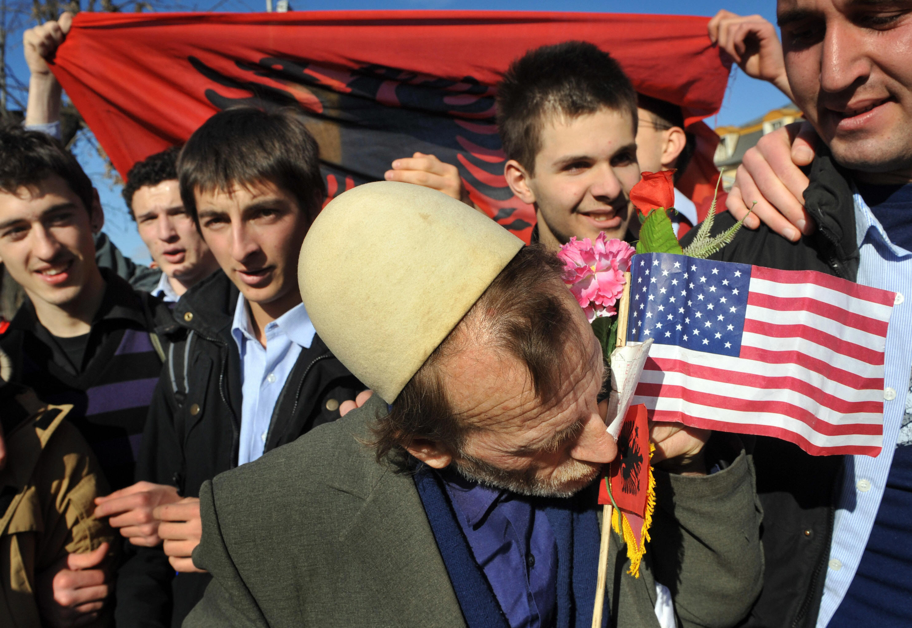 A Kosovan kisses the Albanian and US flags, as people gathered to celebrate in downtown Pristina on February 19, 2008.