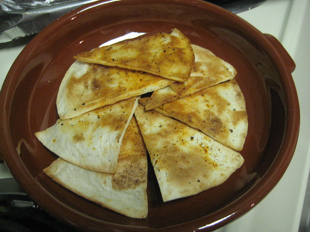 Layering the baked tortillas in a cazuela.
