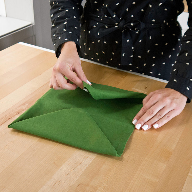pinch your fingers at the center of the square and lift the napkin off the table creating a top fold that runs through the center